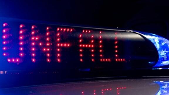 """Das Blaulicht auf einem Fahrzeug der Polizei leuchtet in der Dunkelheit, während auf dem Display der Hinweis """"Unfall"""" zu lesen ist."""