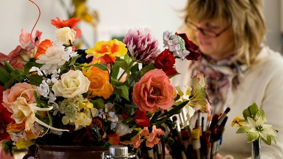 In einer Schauwerkstatt fertigt 2011 eine Mitarbeiterin in Handarbeit Kunstblumen an.