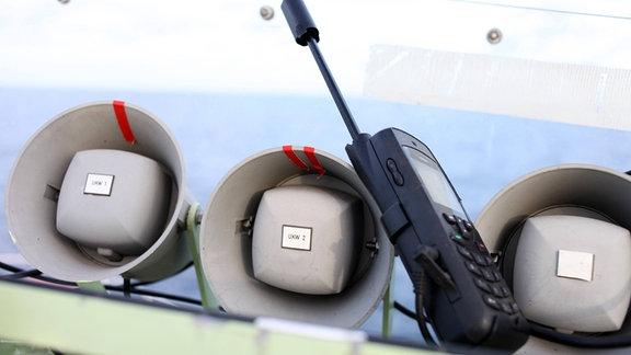 Ein Satellitentelefon zwischen den Lautsprechern der Funkanlage