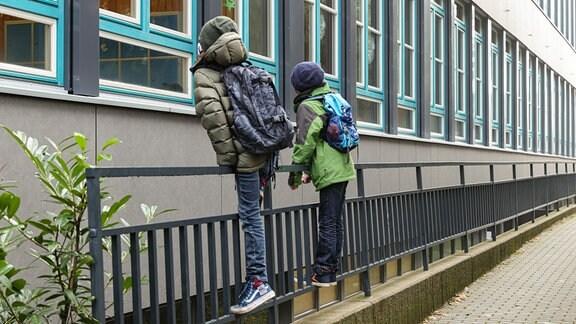 Schüler beobachten vor einem Gymnasium ihre Klassenkameraden durch das Fenster.