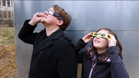Ein Mann und ein Mädchen schauen durch Sofi-Brillen in den Himmel.
