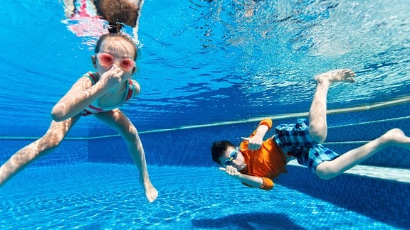 """Zwei Kinder tauchen in einem Schwimmbecken, dazu der Schriftzug """"Sommer, Sonne, Badespaß"""""""
