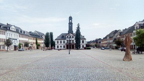 Ein großer gepflasterter Marktplatz mit einem Rathaus mit schlankem Turm in der Mitte.