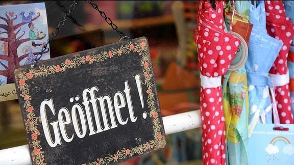 """An einem Geschäft hängt ein Schild auf dem """"Geöffnet"""" steht."""
