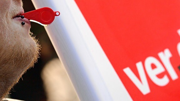 Ein Mann hat bei einem Warnstreik vor dem roten Verdi-Logo eine Trillerpfeife im Mund.