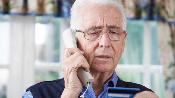 Ein MAnn hat eine Kreditkarte und einen Telefonhörer in der Hand