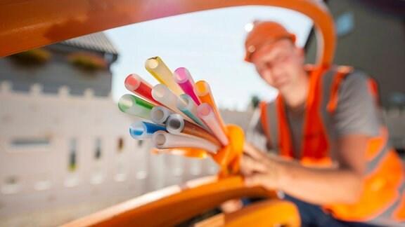 Ein Baubegleiter verlegt ein Breitbandkabel