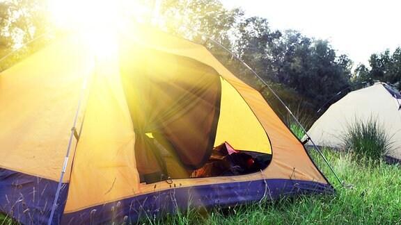 Ein Zelt auf einem Campingplatz bei Sonnenaufgang.