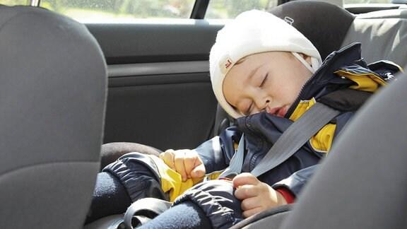 Ein Junge schläft in einem Autokindersitz