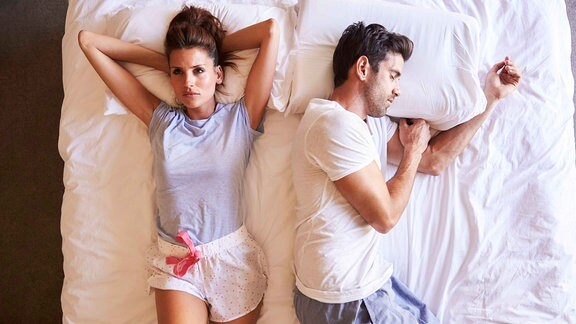 Symbolfoto einer jungen Frau, die schlaflos im Bett liegt