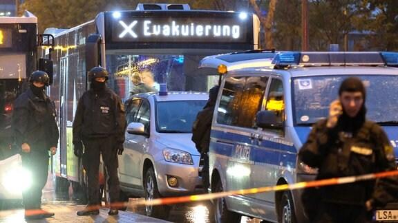 """Ein Bus mit der Aufschrift """"Evakuierung"""" wird von Polizei eskortiert ."""