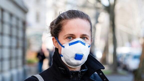 Symbolfoto zum Thema Corona-Pandemie, Covid-19 - Eine Frau traegt eine FFP2 Atemschutzmaske.