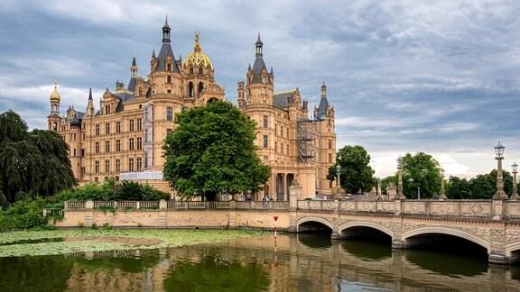 Das Schweriner Schloss spiegelt sich im Wasser.