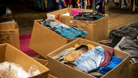 Kisten mit gebrauchter Kleidung warten in einem Secondhand-Laden in New York darauf, preislich bewertet und sortiert zu werden.