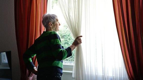 Eine ältere Frau sieht aus dem Fenster