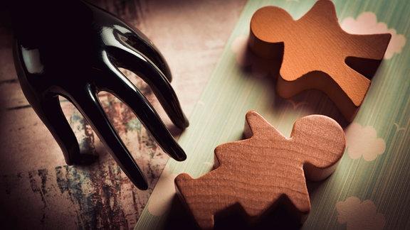 Schwarze Hand und Kinderfiguren