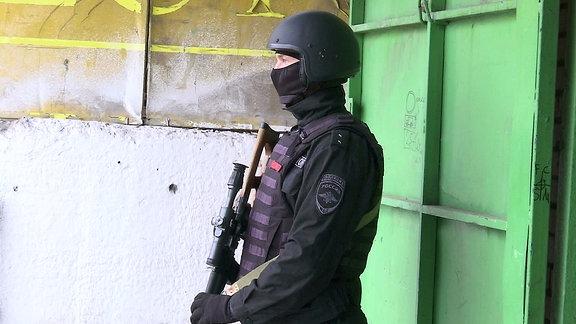 Ein Mitglied der Russischen Garde sichert einen Einsatz gegen Markenfälscher ab