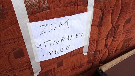 Eine Couch mit einem Zettel mit der Aufschrift ZUM MITNEHMEN - FREE