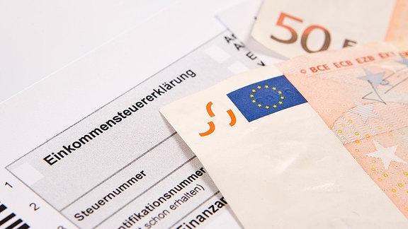 Das Formular der Einkommensteuererklärung und zwei 50-Euro-Scheine liegen auf einem Tisch
