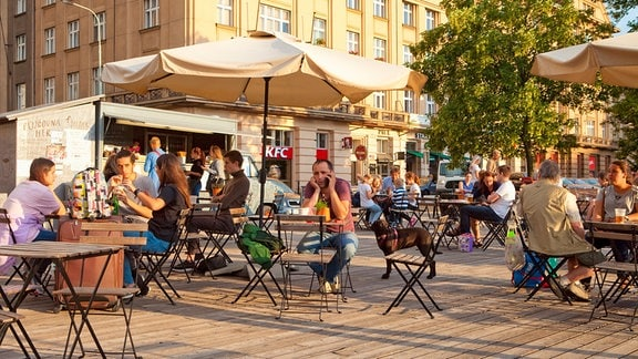 Bei sonnigem Wetter wird in einem Straßenrestaurant in Prag gegessen und getrunken.