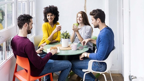Junge Leute sitzen an einem Tisch.
