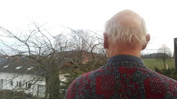 Ein älterer Mann von hinten. Er schaut in die Landschaft.