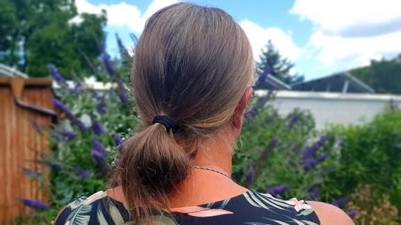 Eine Person im Blumenkleid und mit Zopf steht vor einem Strauch
