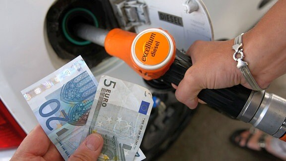 Symbolfoto - Ein Auto wird betankt während ein Mann Geldscheine in der Hand hält.