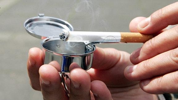 Ein Raucher ascht in einen transportablen Aschenbecher