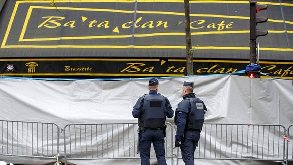 Zwei französische Polizisten stehen an einem Tatort.