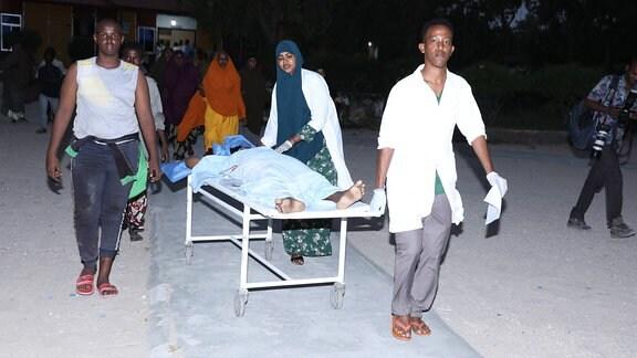 Menschen rollen einen Verwundeten zum Krankensaal