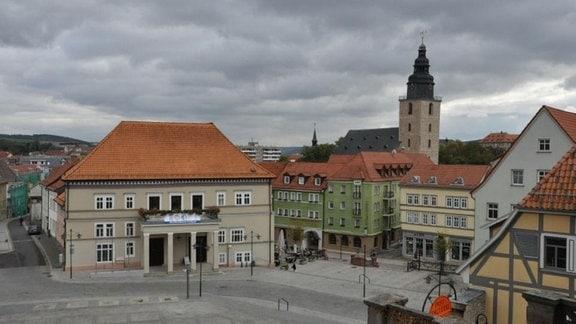 Blick auf das Stadtzentrum von Sondershausen. Am Marktplatz steht das Rathaus, umring von Häuserzeilen. Im Hintergrund steht eine Kirche mit einem hohen Turm.