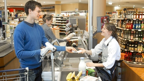 Bezahlen an einer Kasse im Supermarkt