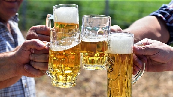 Männer stoßen mit Biergläsern an