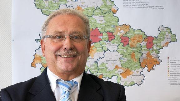Landeswahlleiter Günter Krombholz vor einer Thüringenkarte