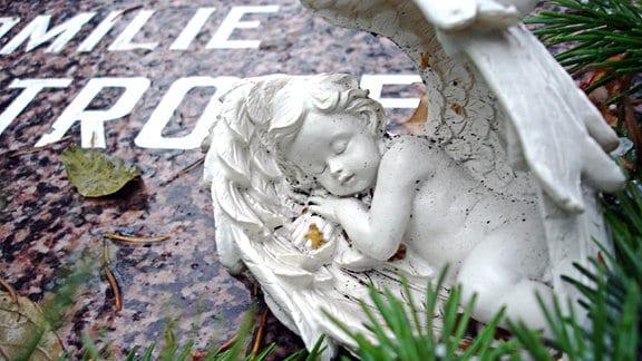 Ein Grabstein, auf dem die Figur eines schlafenden Engels liegt