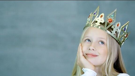 Ein als Prinzessin verkleidetes Mädchen mit verträumten Blick.