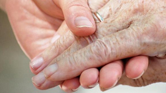 Eine Frau hält die Hand einer Seniorin