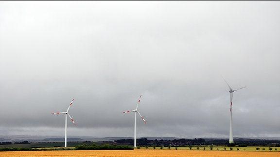 Drei Windräder mit rot-weißen Rotorblättern in weiter Landschaft bei Gewitterstimmung