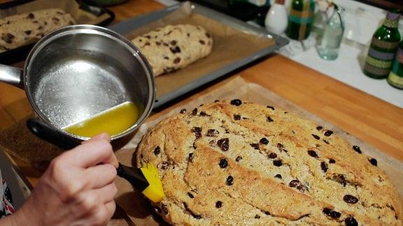 Eine Frau pinselt mit einem Pinsel Butterschmalz auf einen gerade aus dem Ofen geholten Weihnachtsstollen