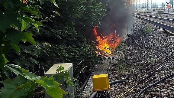 Feuerwerwehrmann auf einem Bahngleis beobachtet einen Kabelbrand.