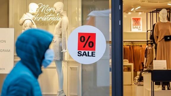 Schaufenster eines Modegeschäfts zur Weihnachtszeit mit Sonderangeboten, Passant mit Schutzmaske in der Essener Innenstadt in Zeiten der Coronakrise beim zweiten Teil Lockdown