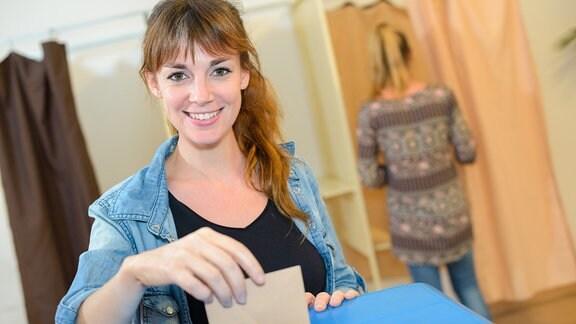 Frau an einer Wahlurne