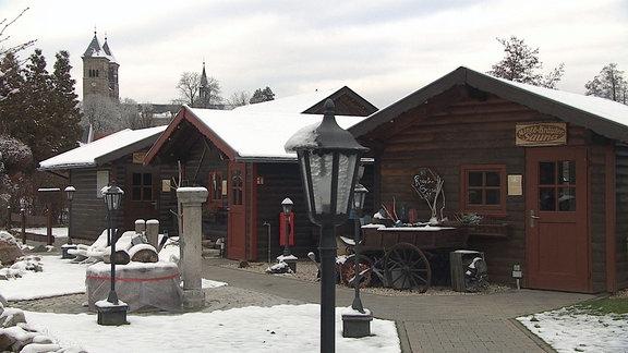 Drei Holzhütten stehen an einem Weg.