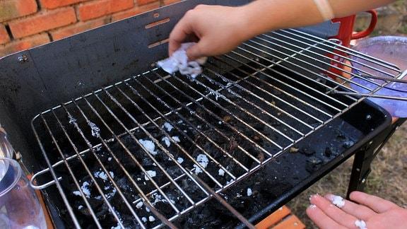 Ein Grillrost wird mit Backpulverpaste gereinigt