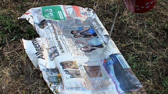 In Zeitung eingewickelter Grillrost wird mit Wasser begossen