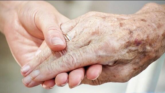 Eine Frau hält die Hand einer Seniorin.