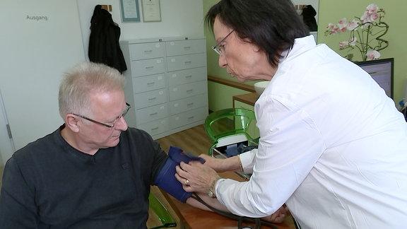 Eine Ärztin legt einem Patienten ein Blutdruckmessgerät an.