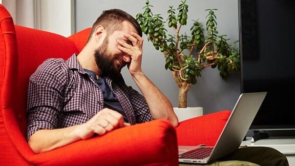 Ein Mann mit einem Computer auf dem Schoß hält sich den Kopf.