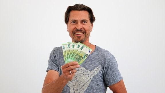 Morgenhahn-Moderator Johannes-Michael Noack von MDR THÜRINGEN hält fünf 100-Euro-Geldscheine in der Hand.